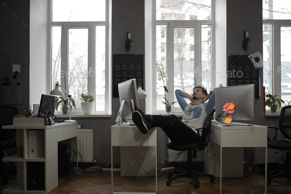 A man thinking of a vacation in a modern office while relaxing - Stock Photo - Images