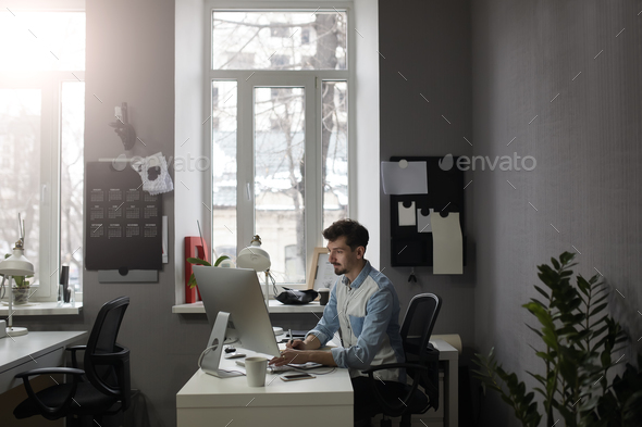 Young intelligent bearded man working at modern loft studio-offi - Stock Photo - Images