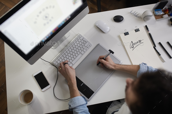 Young male designer using graphics tablet while working with com - Stock Photo - Images