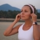 Young Woman Wearing Smartwatch And Wireless Earphones Doing Sports On Beach - VideoHive Item for Sale