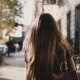 Back View Happy Caucasian Girl with Flying Hair Walking Along Sunny City Street, Living Casual