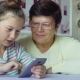 Young Cute Granddaughter Teaching Grandmother How To Use Smartphone at Home - VideoHive Item for Sale