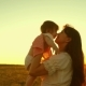 Young and Beautiful Mother with Child Is Playing in Air in Glare of Sunset - VideoHive Item for Sale