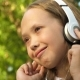Girl in Headphones Listening To Music and Smiling Dancing in Summer Park - VideoHive Item for Sale