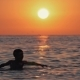 A Child in the Open Sea at Sunset Plays and Learns To Swim. Silhouette of a Boy in the Sea at Sunset - VideoHive Item for Sale