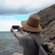 Woman with a Hat Takes Pictures of the Sea on Her Mobile Phone on the Beach - VideoHive Item for Sale