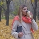 An Elegant Lady In The Autumn Park Holds A Folder Or A Laptop And Drinks Coffee - VideoHive Item for Sale