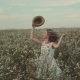 Girl with a Hat in Her Hand Walks in a Field with Field Flowers - VideoHive Item for Sale