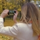 Woman In An Autumn Park With Yellow Foliage Uses A Smartphone and Takes Pictures - VideoHive Item for Sale