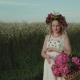 Girl with a Basket of Flowers and a Wreath on Her Head Walks in the Field - VideoHive Item for Sale