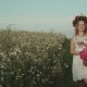 Beauty Woman with a Flowers and a Wreath on Her Head Walks in the Field - VideoHive Item for Sale