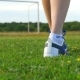 A Girl with Beautiful Slender Legs Goes on a Green Field.  of Women's Feet in Sneakers - VideoHive Item for Sale