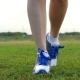 The Girl in Sneakers Is on the Green Grass in the Direction of the Camera. Sports and Outdoor - VideoHive Item for Sale