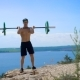 Muscular Crossfit Sportsman in Hat Training with Barbell on the Hill - VideoHive Item for Sale