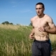 Portrait of a Muscular Shirtless Man Running Across the Field - VideoHive Item for Sale