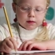 Beautiful Little Girl in Glasses with a Pencil Draws - VideoHive Item for Sale