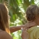 Young Woman in a Tropical Park Puts on Her Son a Mosquito Repellent - VideoHive Item for Sale
