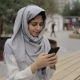 Young Woman in Hijab Texting on a Bench in a City - VideoHive Item for Sale