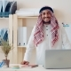 Portrait of a Cheerful Middle Eastern Man Working in the Office for a Laptop. On Her Head Wearing - VideoHive Item for Sale