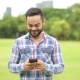 Young Handsome Indian Man In Park Using Mobile Phone - VideoHive Item for Sale