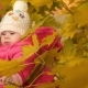 Baby and Mom Smiling Touching Yellow Autumn Leaves in the Park - VideoHive Item for Sale