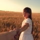 Laughing Girl Runs Across the Field with Wheat Holding a Man's Hand - VideoHive Item for Sale