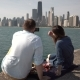 Back View of Young Couple Having Picnic on the Shore of Michigan Lake in Chicago, America. Man Takes - VideoHive Item for Sale