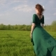 Young Beautiful Woman in a Beautiful Dress Is Standing in a Field at Sunset - VideoHive Item for Sale