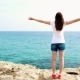Woman Raise Arms Up at Cliff Against Blue Sea - VideoHive Item for Sale
