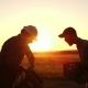 Two Farmers Together Carry a Corn Crop in a Wooden Box at Sunset - VideoHive Item for Sale