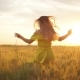 A Girl in a Red Dress Runs Across the Field at Sunset - VideoHive Item for Sale