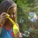 Happy Child Blowing Soap Bubbles in Park. . Stock Footage. - VideoHive Item for Sale