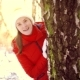 Woman Enjoying Winter Day Outdoors. Happy Girl Hiding Behind Big Tree in Winter Park - VideoHive Item for Sale