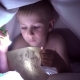 A Child Reads a Book Under Blankets with a Flashlight at Night. Boy with Light Hair and Blue Eyes - VideoHive Item for Sale