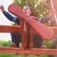 Happy Smiling Boy on a Wooden Swing in the Form of an Airplane in a Park in the Sunlight - VideoHive Item for Sale