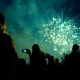 Crowd of People Looks at the Fireworks at Night. Multicolored Pyrotechnic Show on the Holiday - VideoHive Item for Sale