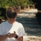 Teen Boy Walking in the Park in the Summer Talking on a Smartphone - VideoHive Item for Sale