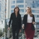 Two Young Attractive Women in Formal Suits Go Against the Background of a Modern Business Center - VideoHive Item for Sale