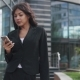 Attractive Business Woman Uses a Smartphone on the Background of a Modern Business Center - VideoHive Item for Sale