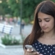 Smart Girl Is Smiling and Browsing the Net on Her Phone on a Riverbank in Summer - VideoHive Item for Sale