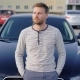 An Attractive Man with a Beard Stands Next To His Car in the Parking Lot - VideoHive Item for Sale