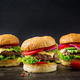 Three hamburger with beef meat burger and fresh vegetables on dark background. Tasty food. - PhotoDune Item for Sale