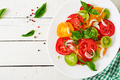 Colored tomato salad with onion and basil pesto. Vegan food. Top view. Flat lay - PhotoDune Item for Sale