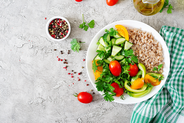 Healthy vegetarian salad of fresh vegetables - tomatoes, cucumber, sweet peppers and porridge - Stock Photo - Images