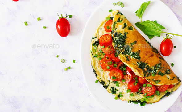 Omelette with tomatoes, spinach and green onion on white plate. - Stock Photo - Images