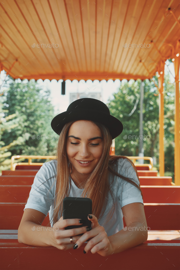 Young hipster girl in trendy hat holding smartphone in hands smi - Stock Photo - Images