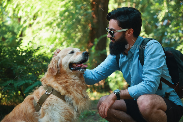 Handsome young man with golden retriver outdoors - Stock Photo - Images