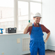 Portrait of happy builder man laughing and making thumbs up at camera in white helmet - PhotoDune Item for Sale