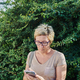 Senior woman using smartphone near bush - PhotoDune Item for Sale
