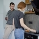 Married Couple in a Kitchen, Woman Is Cooking Scrambled Eggs and Husband Is Talking with Her - VideoHive Item for Sale